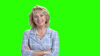 Smiling business woman on green screen. Cheerful elegant woman crossed arms on Alpha Channel background. Female beauty and charm.
