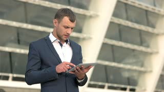 Smiling businessman with a tablet. Man in a suit outdoor. Business and media.
