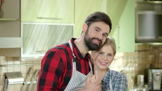 Smiling caucasian couple, kitchen. Man and woman hugging.