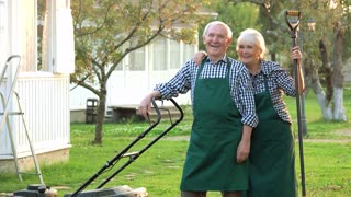 Smiling couple of senior gardeners. Happy people outdoors, summer. Garden maintenance jobs.