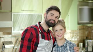 Smiling couple on kitchen background. Happy young woman and man.