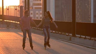 Smiling couple on rollerblades. Woman and man holding hands. Good idea for first date. Sport connects people.