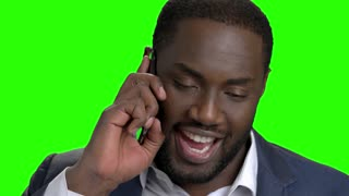 Smiling dark-skinned man talking on phone. Happy afro american businessman talking on mobile phone on chroma key background close up.
