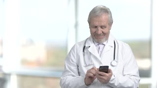 Smiling doctor using his smartphone. Joyful elderly doctor typing a message on his smartphone on abstract blurred background.