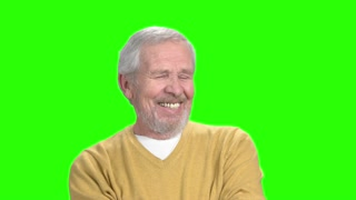 Smiling elderly man, green screen. Cheerful senior man in yellow sweater smiling on chroma key background. Human facial expressions of positivity.