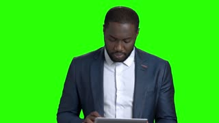 Smiling entrepreneur using digital tablet. Cheerful afro-american businessman working on pc tablet and looking at camera on chroma key background.