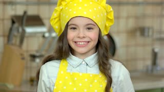 Smiling girl in chef uniform. Cheerful caucasian child. Cooking projects for kids.