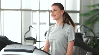 Smiling girl running on a treadmill. Slow motion pretty goman running on treadmill and listening music with earphones at fitness club.