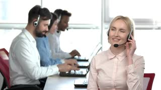 Smiling lady talking on headset in the office. Lady call center worker in front of colleagues, front view.
