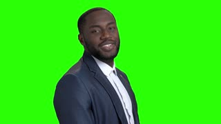 Smiling macho-man on green screen. Portrait of sexy afro-american businessman is flirting on Alpha Channel background. Invitation for a date.