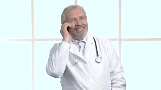 Smiling male doctor talking on mobile phone. Happy cheerful medical specialist talking on his phone at work.