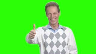 Smiling man showing thumb up. Joyful caucasian man making thumb up on green background. Gesture of succsess.