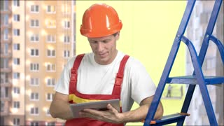 Smiling manual worker with pc tablet. Portrait of happy worker in uniform holding digital tablet, buildings background. Construction, building, people and maintenance concept.