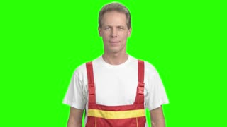 Smiling mature builder, green screen. Positive middle-aged contruction worker crossed arms standing on alpha channel background.