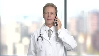 Smiling mature doctor with mobile phone. Cheerful middle-aged doctor talking on phone, blurred background.