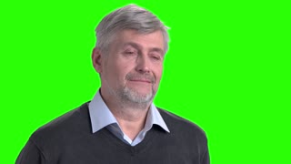 Smiling mature man on green screen. Pensive middle-aged man is smiling on chroma key background. Good memories concept.