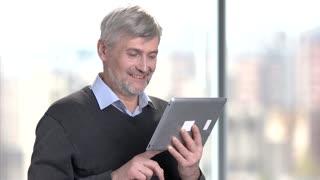Smiling mature man using digital tablet. Handsome senior man talking via internet using computer tablet on blurred background.