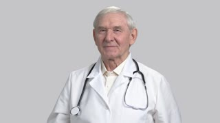 Smiling old senior doctor with pill can and thumb up. Therapist with stethoscope and vitamins in grey isolated background.