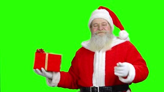 Smiling santa's holding the present and pointing at it. Santa with gift in front of green hromakey background.