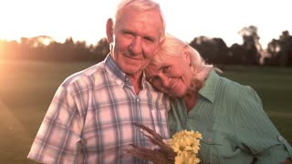 Smiling senior couple with bouquet. Happy elderly man and woman. Time and feelings. Joy of heart.