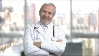 Smiling senior doctor on blurred background. Cheerful older doctor looking at camera with crossed arms.