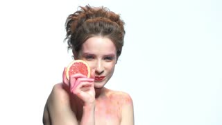 Smiling woman holding grapefruit slice. Girl wearing colorful makeup. How to make dieting easy.