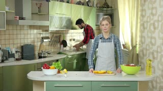 Smiling woman in the kitchen. Girl and guy indoors. Recipes to cook together.