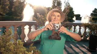Smiling woman with a camera. Lady on background of nature. Make a memorable photo. Give me a smile.