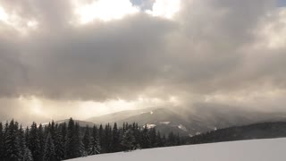 Snowstorm in the mountains. Bad weather. Sun breaks through the dark clouds.