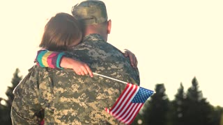 Soldier in camoubackgrounde hugging daughter outdoors, back view. Girl see off father huging him before military mission.