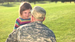 Soldier in camoubackgrounde hugging his daughter in the park. Caucasian little girl saluting brave US soldier.