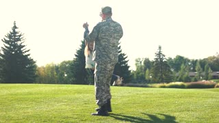 Soldier in camoubackgrounde spinning his daughter around in the park. Outdoor portrait of happy father in military uniform holding his daughter's hands and spinning around.