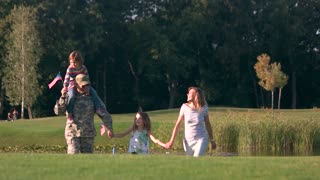 Soldier in camoubackgrounde with his family in the park. Happy walking family holding hands with military father.