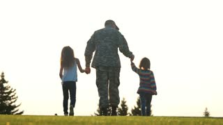 Soldier with little girls walking in the park, back view. Military man holding hands of daughters outdoor in the evening.