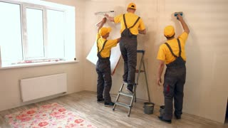 Specialists wallpapering in the house. Brigade of craftsmen making renovation.