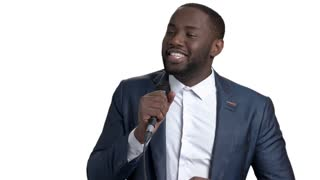 Speech of a black businessman. African american young man in suit speaking with microphone against white isolated background.