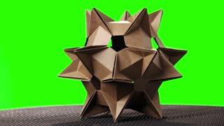 Spiky origami model on green screen. Brown cosmic satellite made from paper. Japanese paper folding art.
