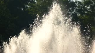 Splashes of fountain in motion. Water and sunshine outdoor.