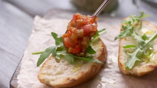 Spoon lays vegetables on bread. Toasts with vegetables and herb. Delicious bruschetta served at bistro. Dish from italian cuisine.