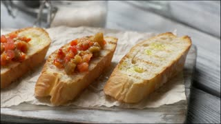 Spoon puts vegetables on bread. Snack on wooden board. Bruschetta served at local bistro. Healthy food from italian cuisine.