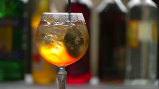 Spoon slowly mixes beverage. Wineglass filled with drink. Chilled aperol spritz. Dry wine and soda water.