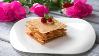 Spoon smears sauce on plate. White plate with raspberry dessert. Sweet sauce for traditional millefeuille. Pastry from french cuisine.