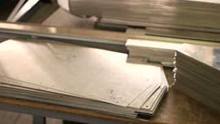 Stack of thin steel parts. Metal sheets on the table. Light aluminium alloys.