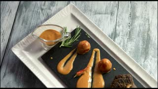 Steak, sauce and vegetables. Stone tray with food. Special recipe of veal.