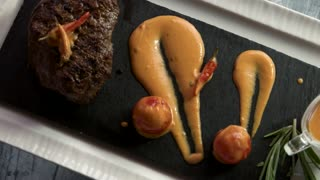 Steak with vegetables and sauce. Food on black stone tray.