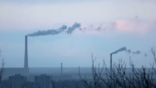 Steaming factory tubes in the city. Evening industrial city, blue photo.