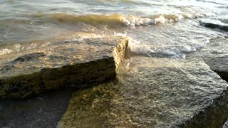 Stones and sea waves. Foamy water in slow-mo.