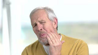 Stressed man with terrible toothache. Close up frustrated senior man touching his cheek because of strong tooth ache, blurred background.