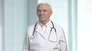 Stressed old angry physician having headache. Senior health care professional doctor with stethoscope. Blurred windows with louvers background.