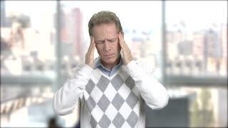 Stressed tired man having a bad headache. Mature man having terrible headache, window city background.
